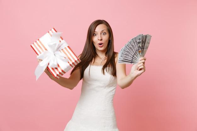 Stupita donna scioccata in abito bianco che tiene in mano un sacco di dollari, denaro contante, scatola rossa con regalo, regalo