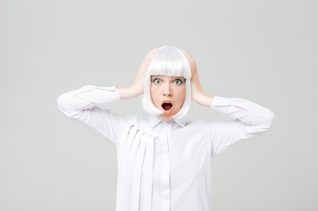 頭に手を添えて金髪のかつらで驚いたショックを受けた若い女性