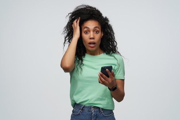 ミントtシャツの長い巻き毛を持つ驚いたショックを受けた若い女性は頭に手を保ち、灰色の壁に隔離された携帯電話を使用しています