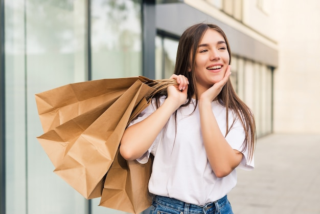 Acquirente stupito che apre la bocca tenendo le borse della spesa guardando le offerte speciali nei negozi e indicando la strada