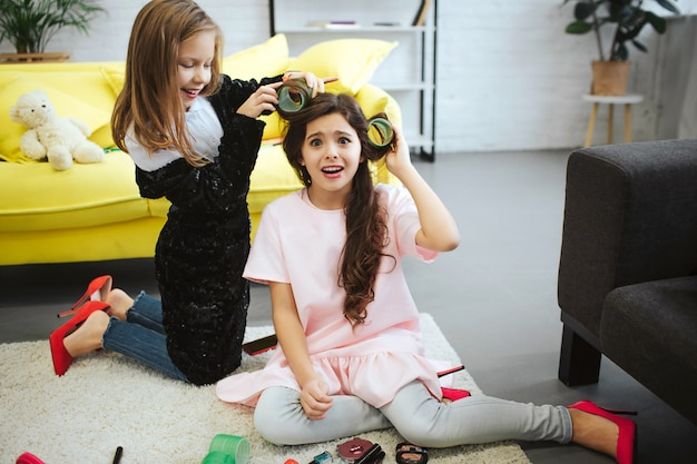 Amazed small girl look. she suffer from pain. her friend stand on knees and wrap hair on curler. she has fun. girls wear clothes for adult women.