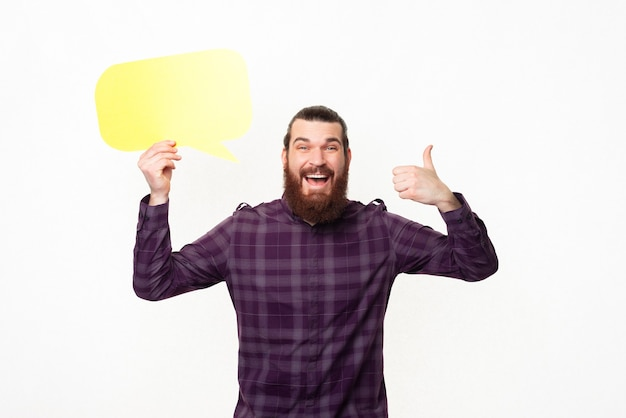 Изумленный улыбающийся бородатый мужчина показывает палец вверх и держит желтый речевой пузырь