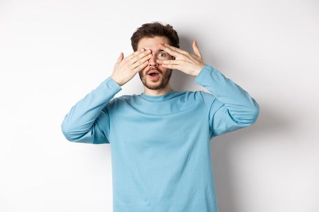 손으로 눈을 덮고 있지만 흰색 배경 위에 서있는 멋진 뭔가에 손가락을 통해 엿보기 놀란 웃는 남자
