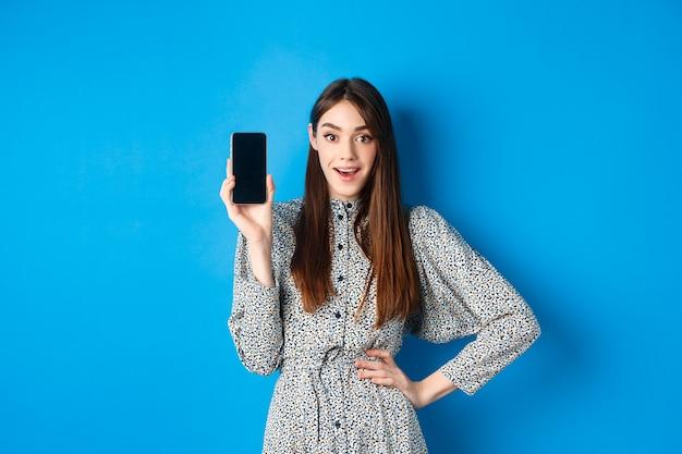 Пораженная улыбающаяся женщина показывает пустой экран смартфона, выглядит впечатленным, рекомендует онлайн-промо, синий.
