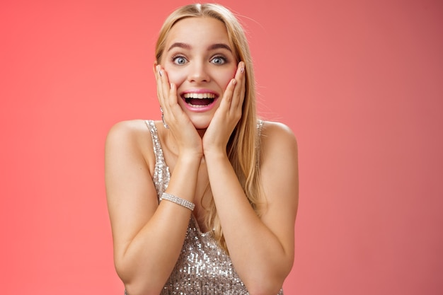 Amazed speechless excited attractive young woman blond long hair press palms cheeks blushing amused cannot believe see popular super star glancing thrilled amazement, surprised red background.