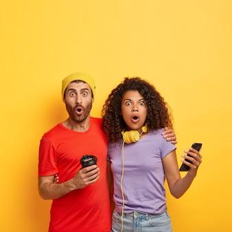 Coppia elegante stupita in posa contro il muro giallo con gadget