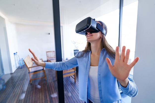 Amazed surprised young woman with virtual reality glasses touching the air during the vr experience game at home. future technology concept