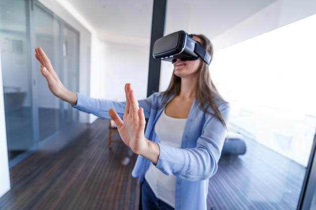 Amazed surprised young woman with virtual reality glasses touching the air during the vr experience game at home