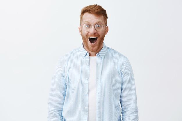 Uomo rosso gioioso stupito ed elettrizzato con barba in occhiali e camicia, che lascia cadere la mascella per lo stupore e la felicità, sorride ampiamente e guarda affascinato