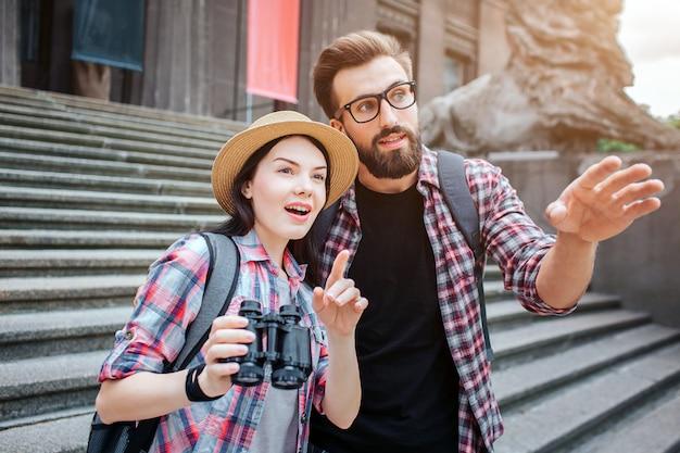 Изумленные туристы стоят перед лестницей. они указывают вперед. женщина держит бинокль. они в городе. бородатый парень носит очки.