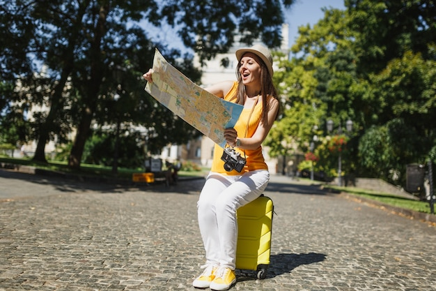 Amazed traveler tourist woman in yellow clothes hat sitting on suitcase looking on city map search route in city outdoor. girl traveling abroad to travel on weekend getaway. tourism journey lifestyle.