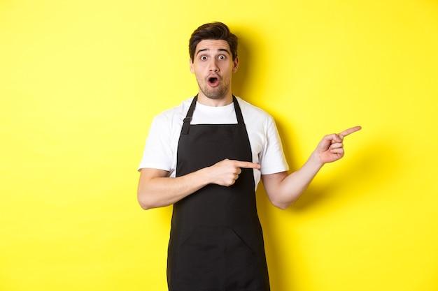 Пораженный официант в черном фартуке показывает промо-предложение, показывает пальцем вправо и выглядит удивленным, стоит в униформе у желтой стены