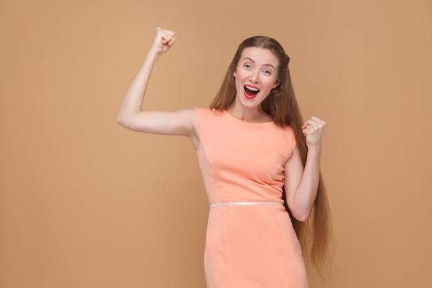 Пораженная девушка-победитель показывает знак победы. портрет эмоциональной милой, красивой женщины с макияжем и длинными волосами в розовом платье. закрытый, студийный снимок, изолированный на светло-коричневом или бежевом фоне.