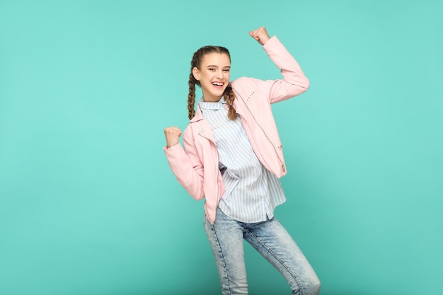 Amazed winner portrait of beautiful cute girl standing with makeup and brown pigtail hairstyle in striped light blue shirt pink jacket. indoor, studio shot isolated on blue or green background.