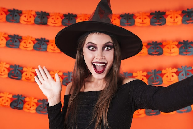 Amazed witch girl in black halloween costume smiling and waving hand at camera isolated over orange pumpkin wall