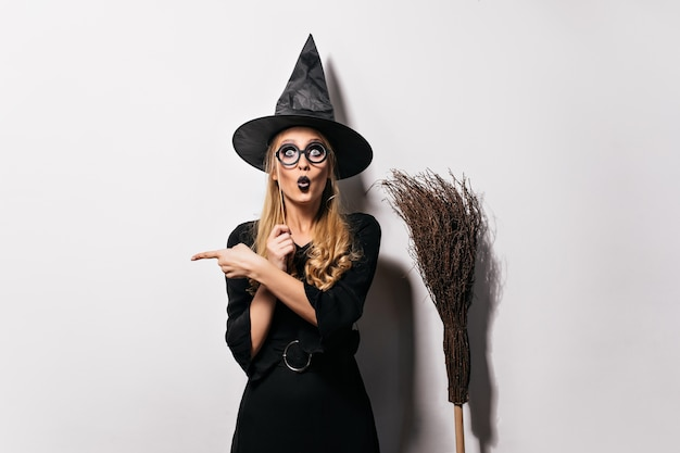 Amazed wizard in glasses standing on white wall. funny emotional witch posing with hat and broom.