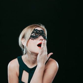 Amazed woman in dark carnival mask