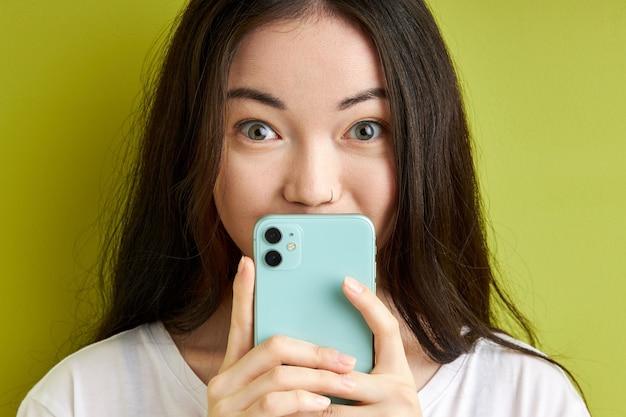 녹색 파스텔 배경에 고립 된 읽기 sms 메시지를 숨기고 놀란 여자, 캐주얼 흰색 티셔츠를 입고 뭔가를 읽은 후 충격에 서서