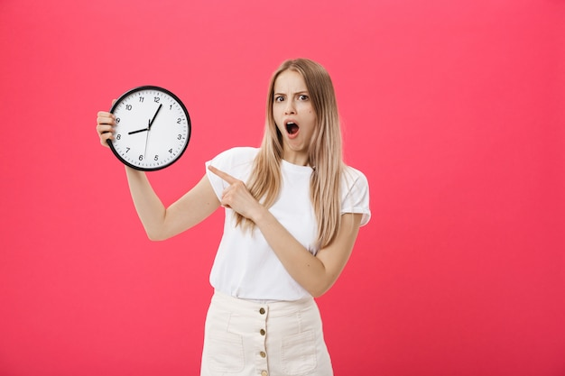 Amazed woman holding clock. surprised woman in white t-shirt holds black clock. retro style. saving time concept. summer sale. discount. isolated on pink background.
