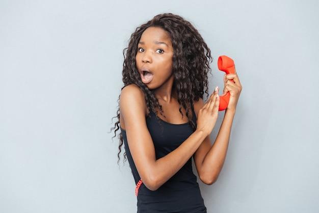 Пораженная женщина, держащая ретро-телефонную трубку и прикрывающая микрофон над серой стеной