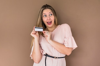 Amazed woman in dress standing with credit card