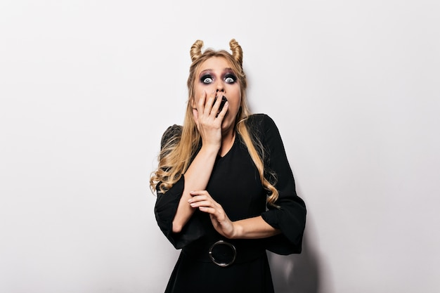 Пораженная женщина в элегантном платье позирует на хэллоуин. красивая ведьма, выражающая удивленные эмоции.