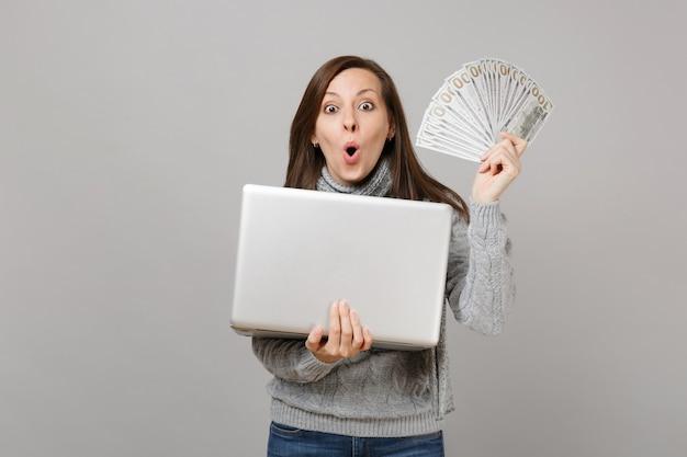 灰色の背景に分離されたたくさんのドル紙幣現金お金を保持しているラップトップpcコンピューターで作業しているセーターの驚いた女性。寒い季節のコンセプトをコンサルティングする健康的なライフスタイルのオンライン治療。