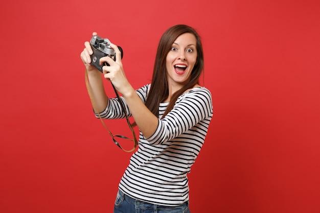 赤い背景で隔離のレトロなビンテージ写真カメラで自分撮りショットを撮って驚いて、口を大きく開いたままにして驚いた女性。人々の誠実な感情のライフスタイルの概念。コピースペースをモックアップします。