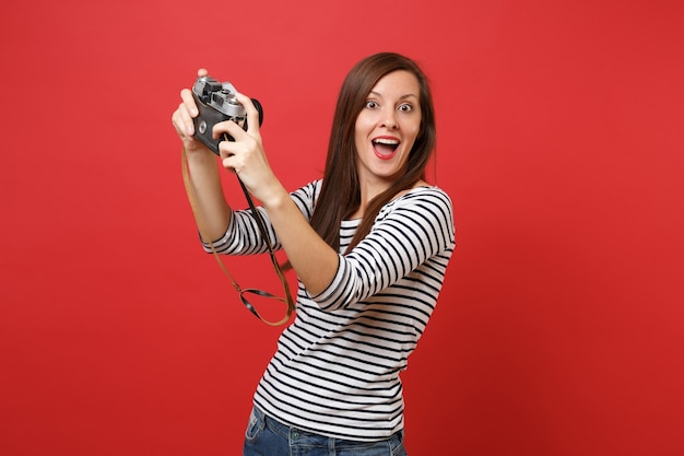 Amazed woman keeping mouth wide open looking surprised doing taking selfie shot on retro vintage photo camera isolated on red background. people sincere emotions lifestyle concept. mock up copy space.