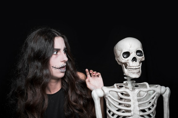 Amazed woman looking at skeleton
