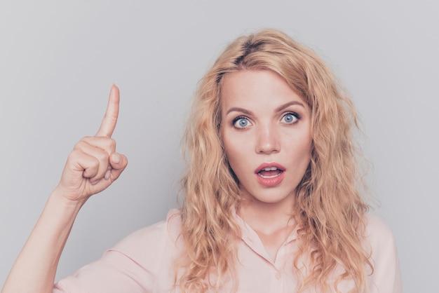 グレーに分離された1本の指を上向きに驚かれる女性