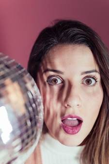 Amazed woman standing with disco ball