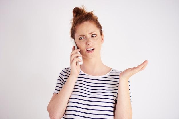 携帯電話のショットで話している驚いた女性