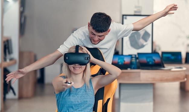 Пораженная женщина пробует очки vr и садится на интерактивное сиденье vr. в руке держит пульт дистанционного управления.