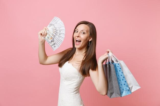 La donna stupita in abito bianco tiene in mano un sacco di dollari, denaro contante, borse multicolori con acquisti dopo lo shopping