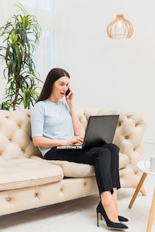 Amazed woman with laptop on couch talking by phone