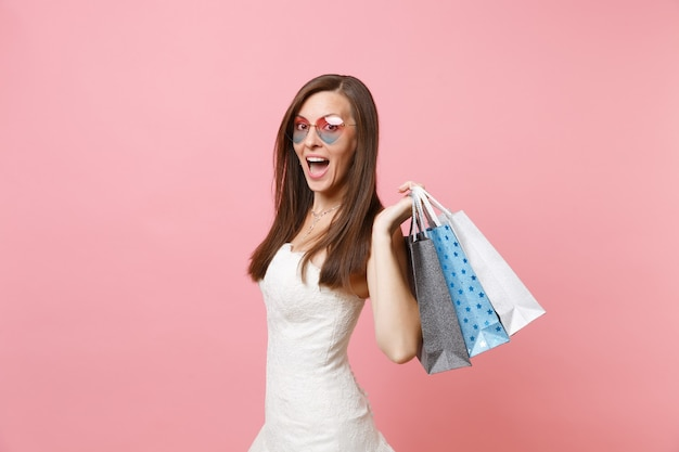 Amazed woman with opened mouth in white dress, heart glasses holding multi colored packages bags with purchases after shopping