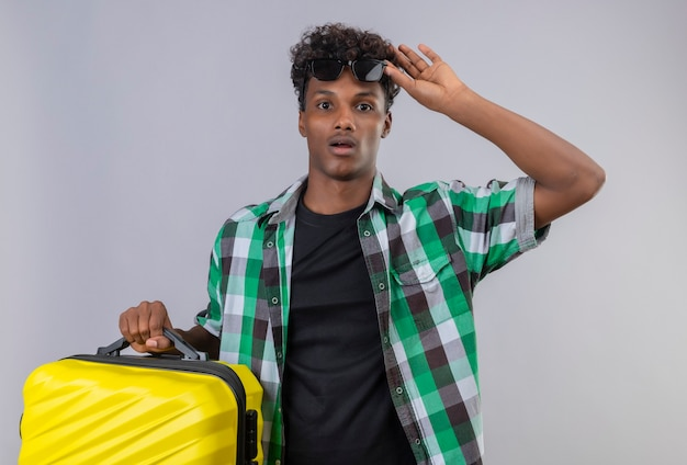 Amazed young african american traveler man holding suitcase taking off sunglasses from amazement