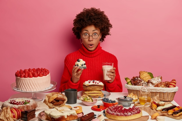 Amazed young afro woman enjoys eating fancy delicious cupcake with yoghurt, enjoys festive dinner, shocked how much calories she ate, wears red sweater, tastes creamy dessert