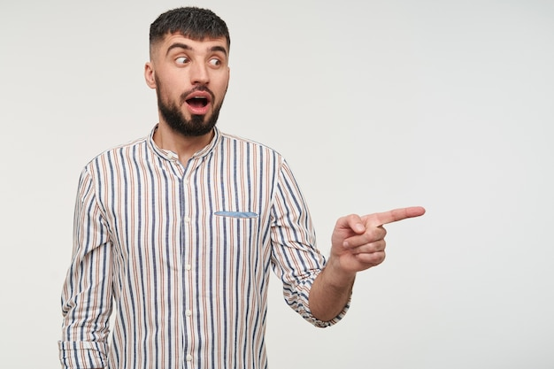 Пораженный молодой привлекательный темноволосый парень с короткой стрижкой удивленно смотрит в сторону с широко открытыми глазами и открытым ртом, держа указательный палец поднятым, стоя у белой стены