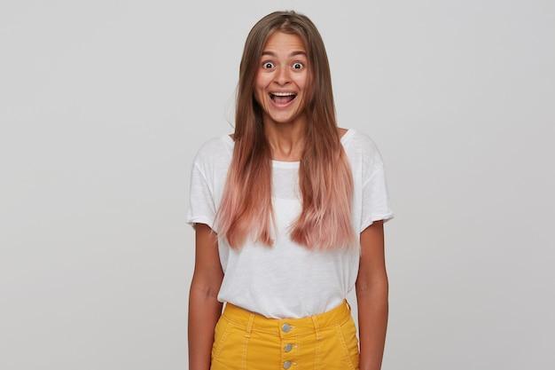 Пораженная молодая привлекательная длинноволосая блондинка смотрит с широко открытыми глазами и открытым ртом, держа руки вдоль тела, стоя у белой стены