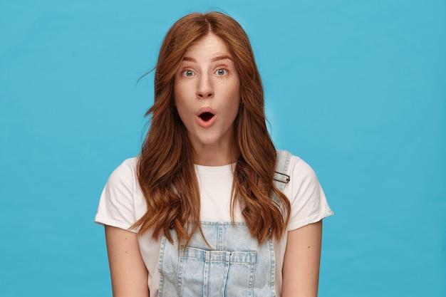 青い背景の上にポーズをとっている間手を下に保ち、広い口を開いてカメラを感情的に見て波状のセクシーな髪を持つ驚くべき若い魅力的な女性