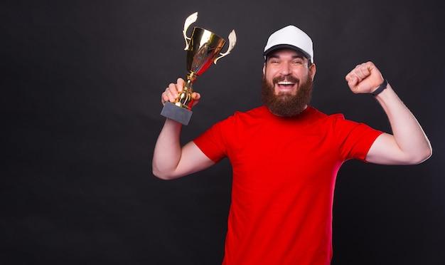 승리를 축하하고 검정 배경 위에 챔피언 컵을 들고 놀란 젊은 수염 난된 남자