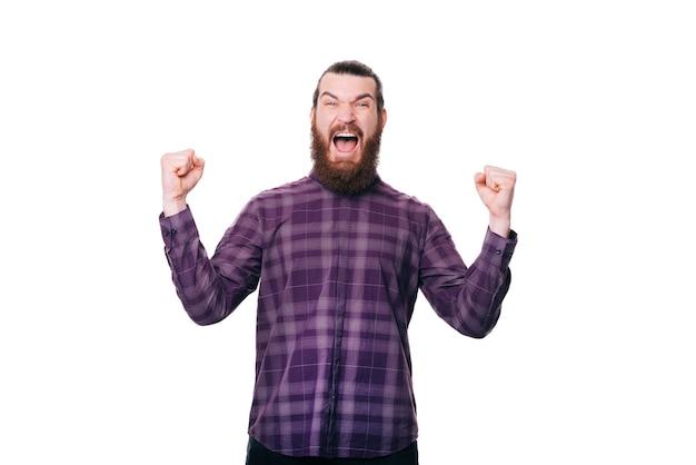 勝利を祝い、叫んで驚いた若いひげを生やした男