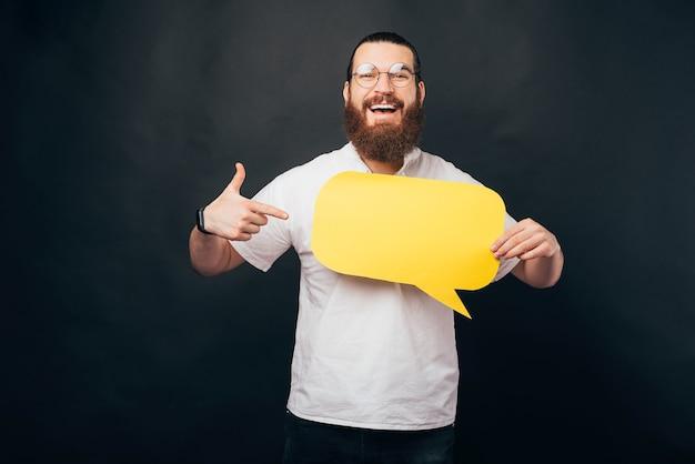 Пораженный молодой бородатый мужчина, указывая на пустой желтый речевой пузырь
