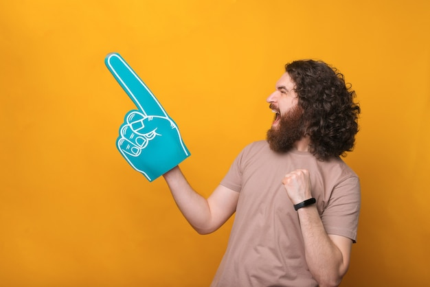 Amazed young bearded man pointing away with fan foam glove over yellow
