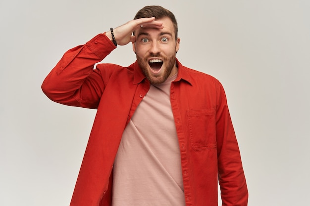 Amazed young bearded man in red shirt with opened mouth keeps hand on forehead and looking far away on distance over white wall