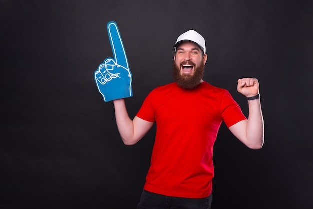 Amazed young bearded man in red t-shirt celebrating and pointing with fan foam glove