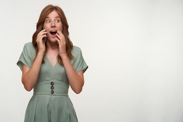 Amazed young beautiful female with red hair posing, opening mouth widely and covering it with hand, holding smartphone by her ear