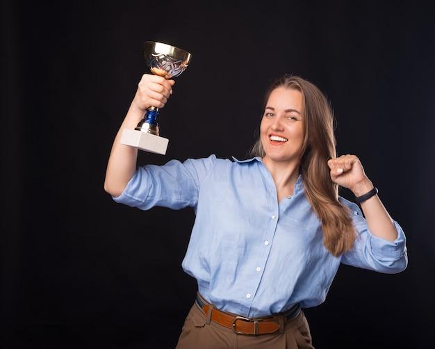 Пораженная молодая бизнес-леди держит чемпионский кубок и празднует победу